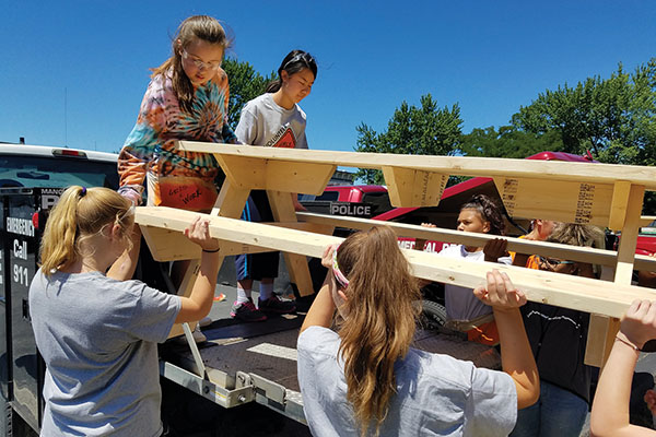 Group of girls lifting a wood table onto a trailer