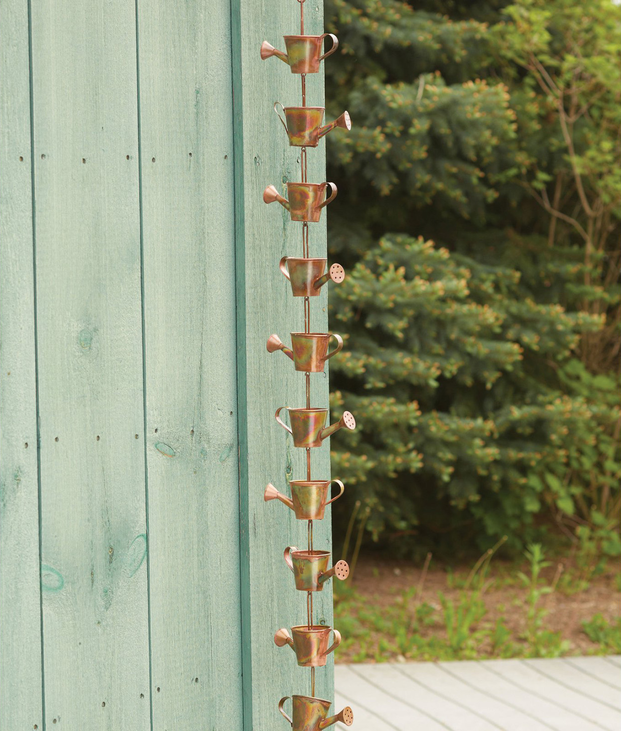 Copper rain chain with small copper watering cans in front of structure with pale teal siding