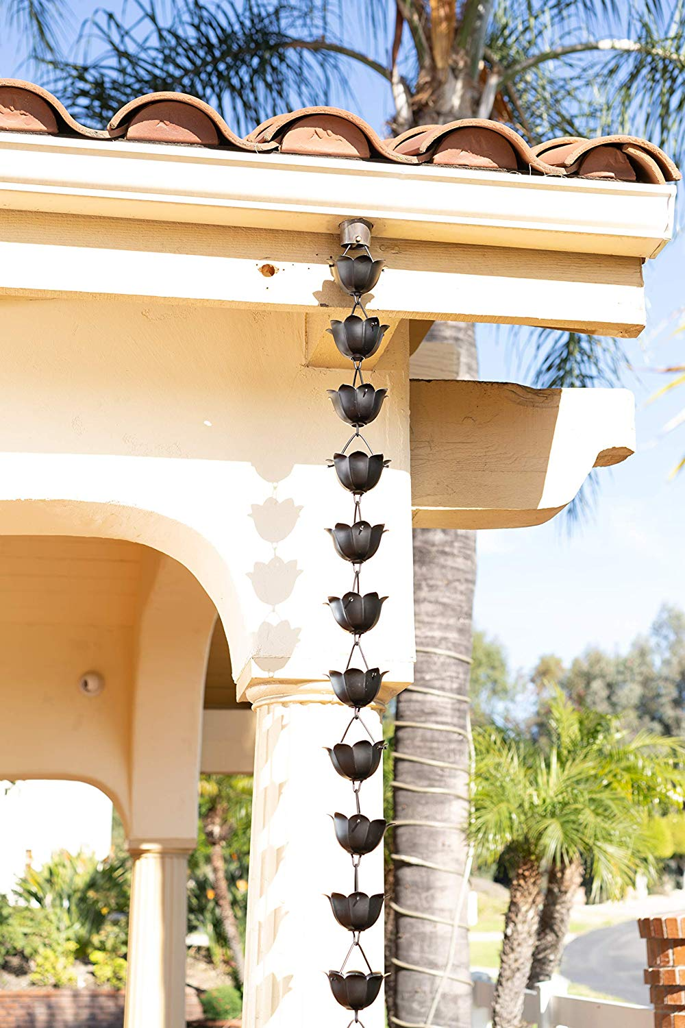 Dark brown matte rain chain with lotus-shaped cups hanging from a Southwestern-style home