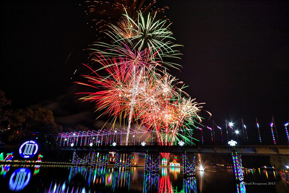 Fireworks and Christmas lights over a river.