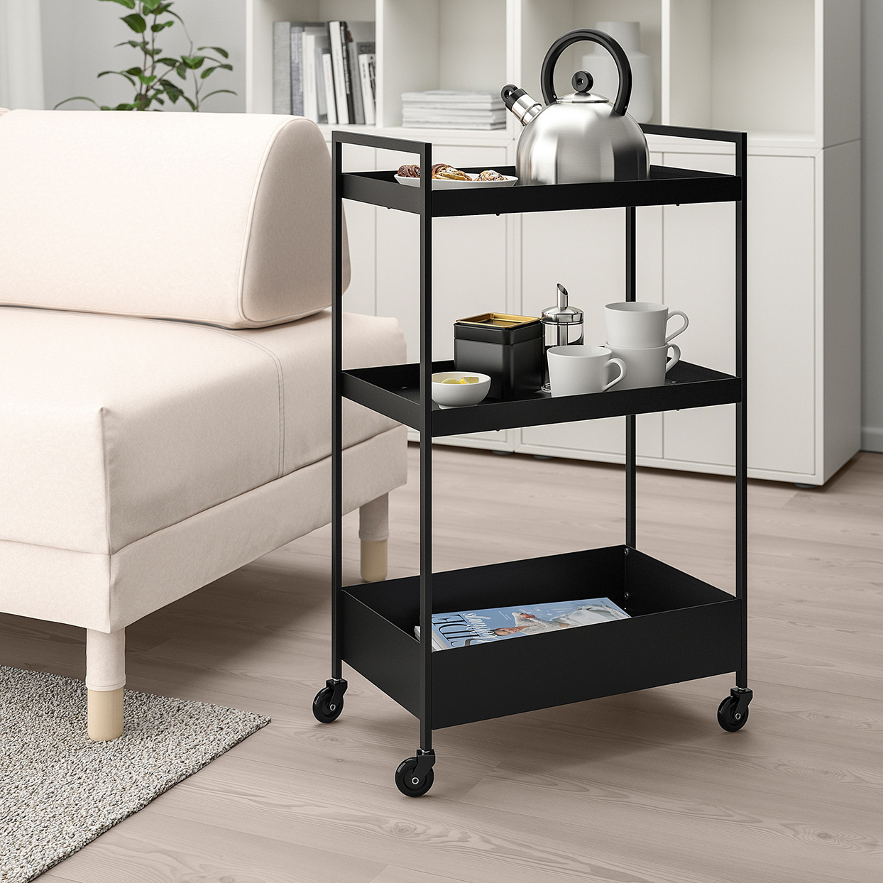Black metal rolling storage cart holding coffee mugs and kettle next to white sofa
