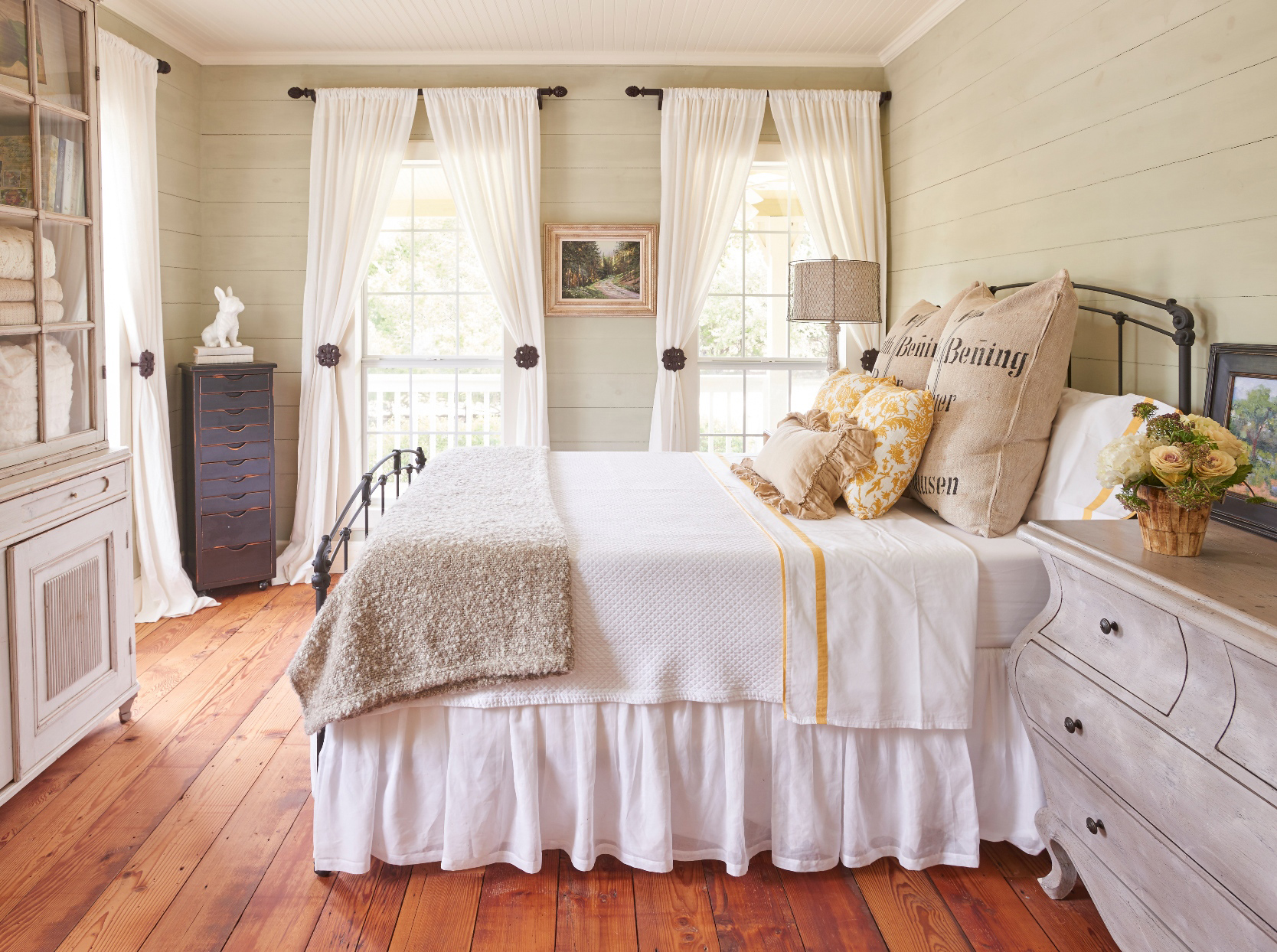 Interior of bedroom with blanket and pillows arranged on bed
