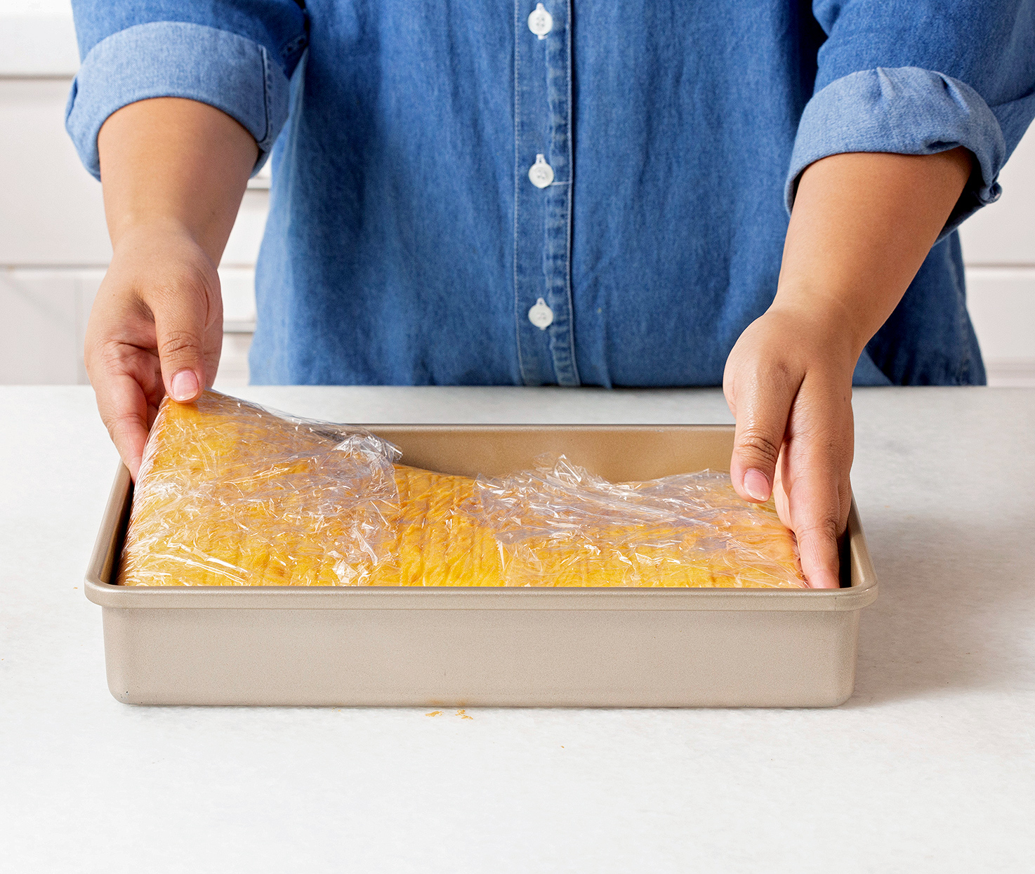 placing plastic-wrapped cake in pan