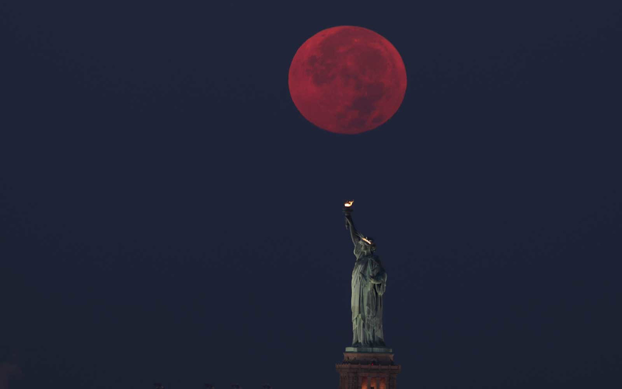 red full moon over the statue of liberty