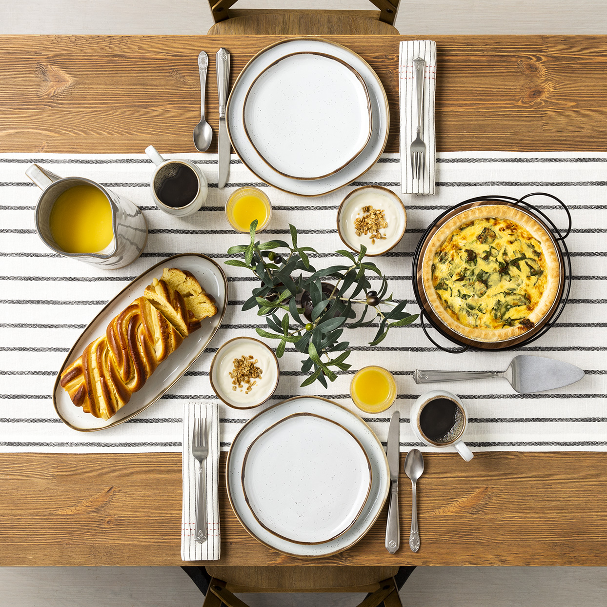 Overhead shot of dining table with black and white striped table runner and stoneware dishes