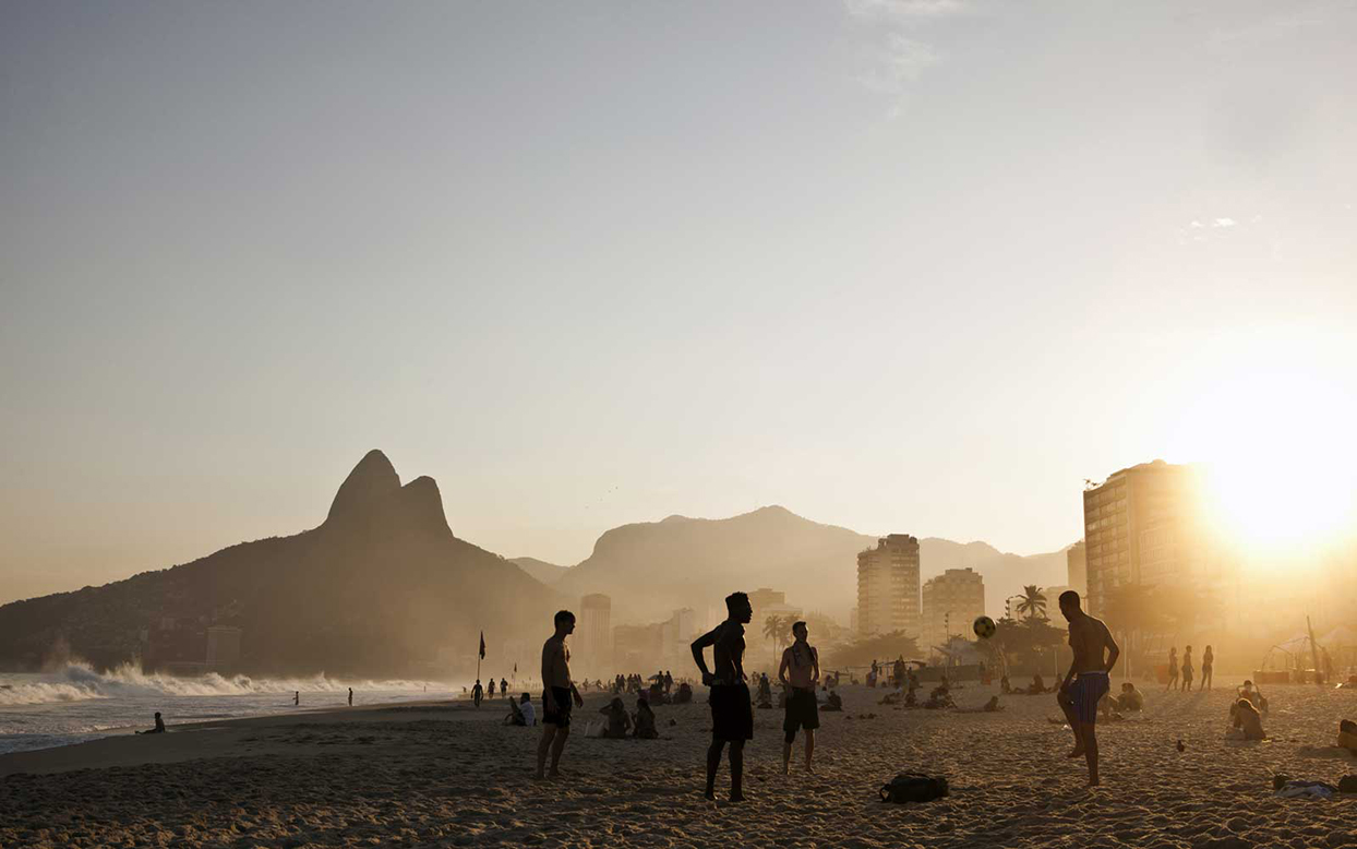people playing soccer on a beach at sunset