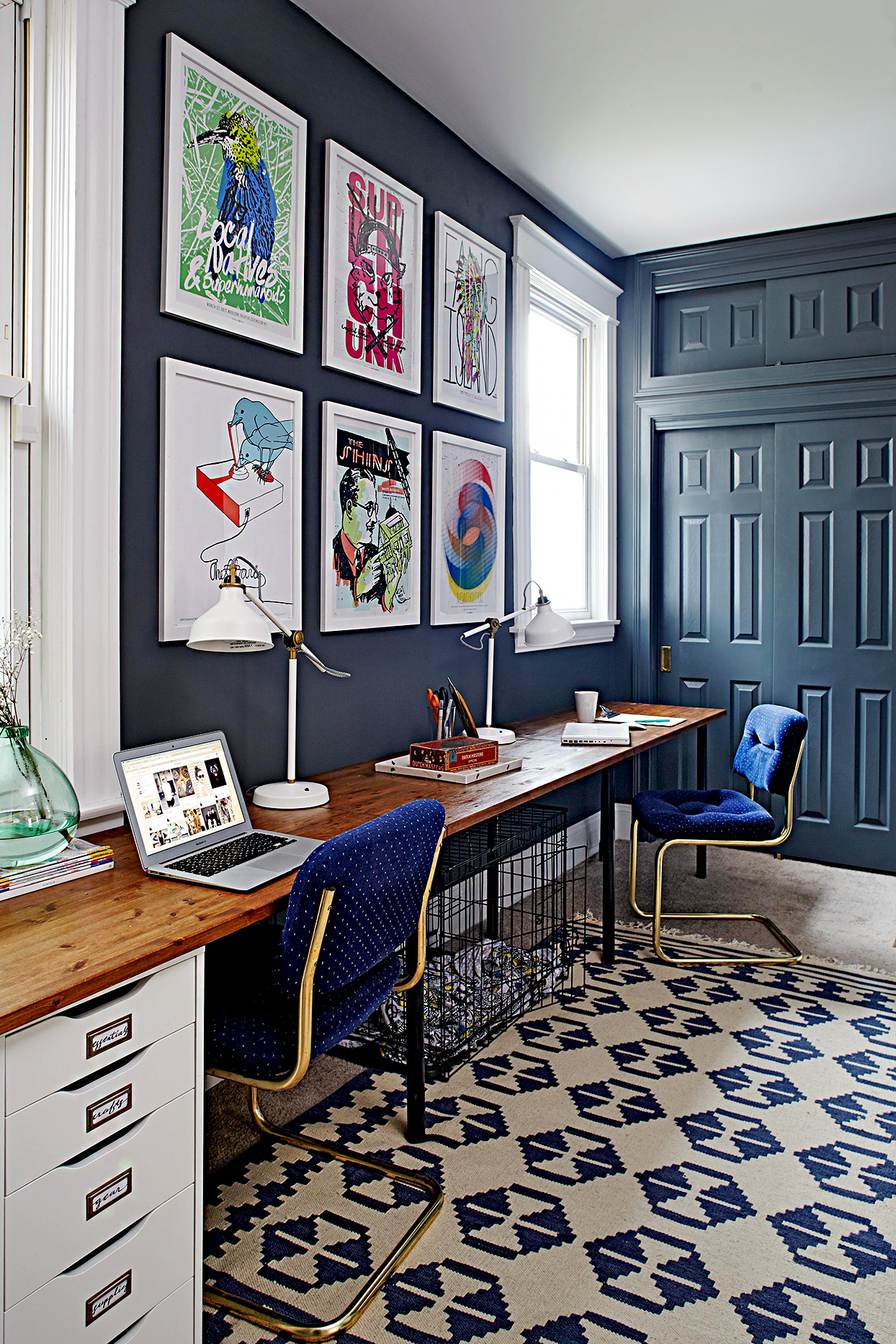 Office area with dark blue walls and large artwork