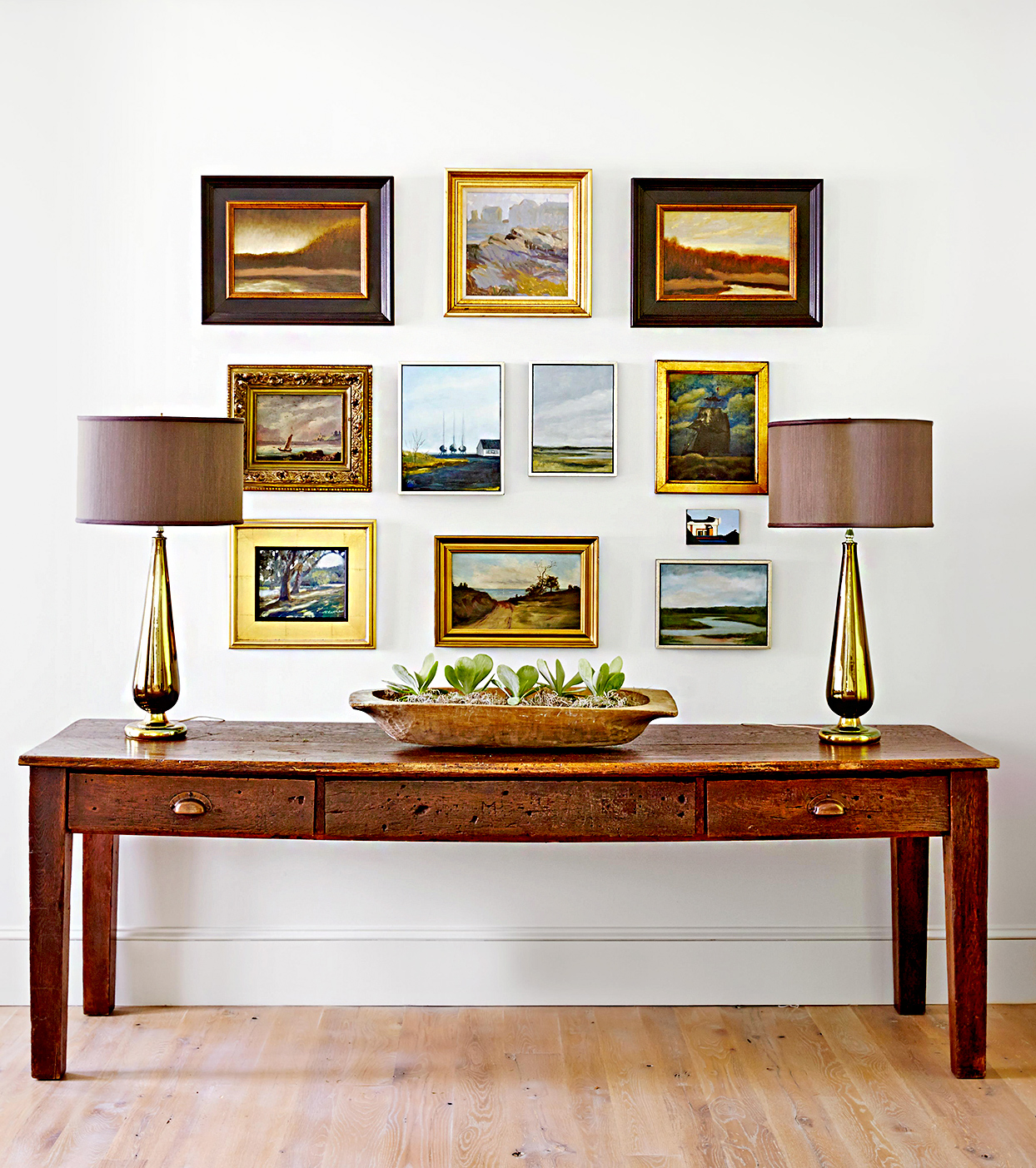 Table with lamps and multiple framed landscapes