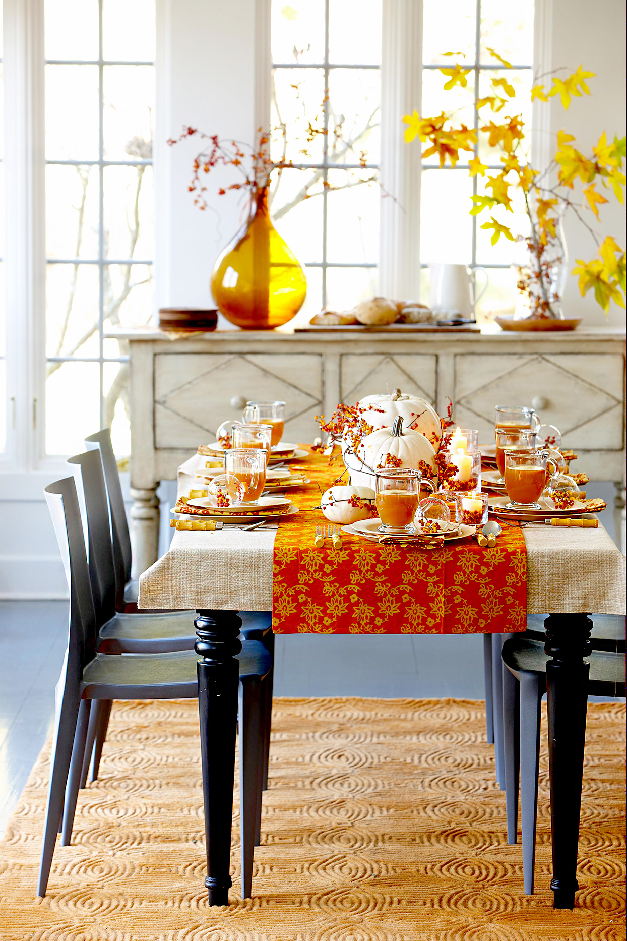 Dining table with orange table runner and pumpkin centerpiece