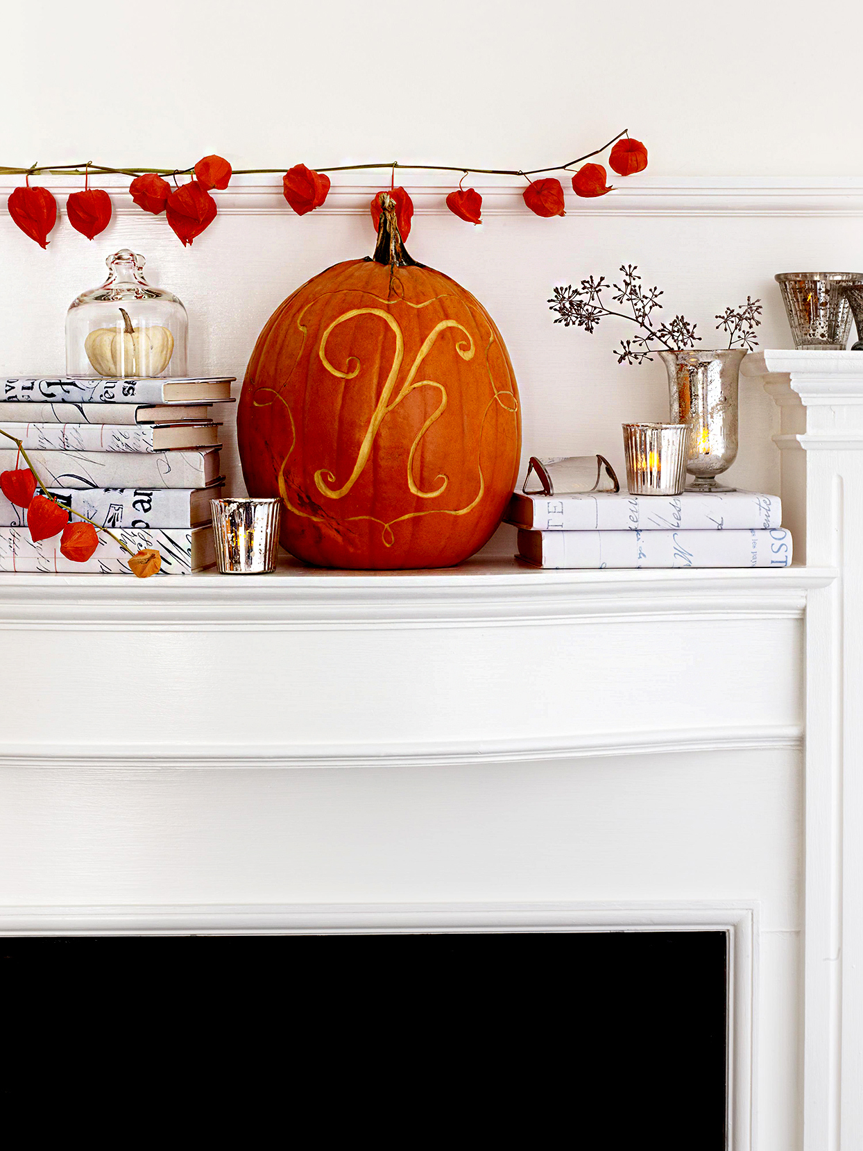 """Fall décor with pumpkin with """"K"""" carved and books"""