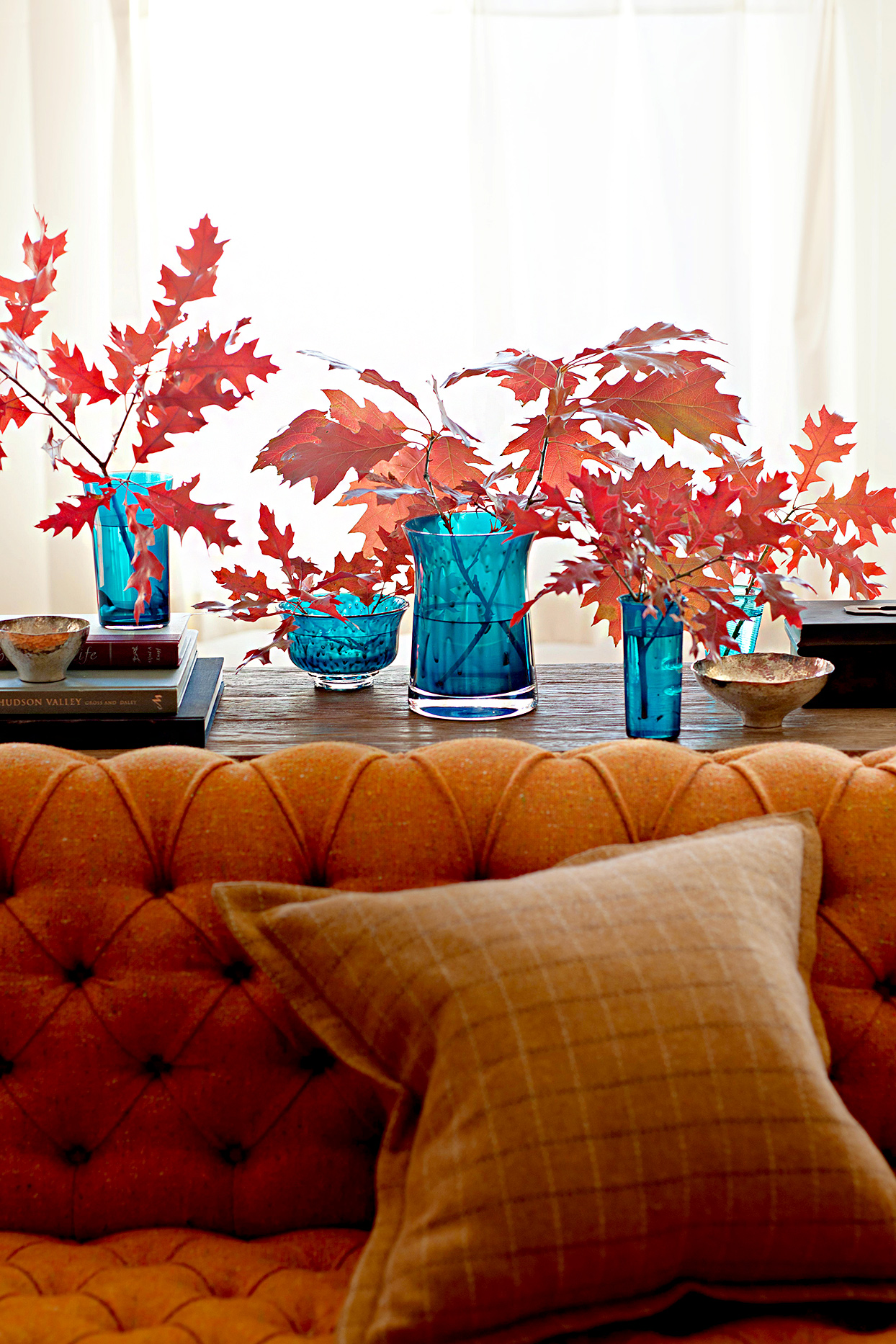 Fall leaves in blue glass vases behind couch