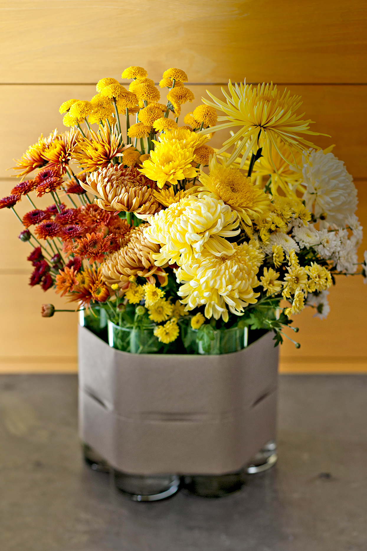 Yellow, orange, and red flowers in multiple vases tied together