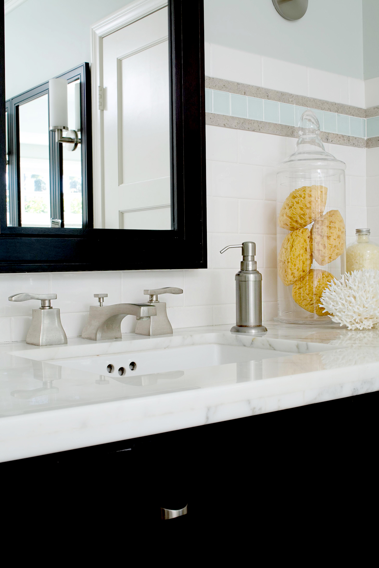 Marble bathroom sink with glass container and sponges