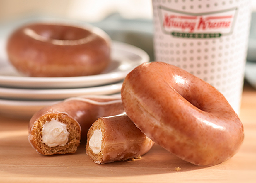 Krispy Kreme Pumpkin Spice donuts on table with coffee in background