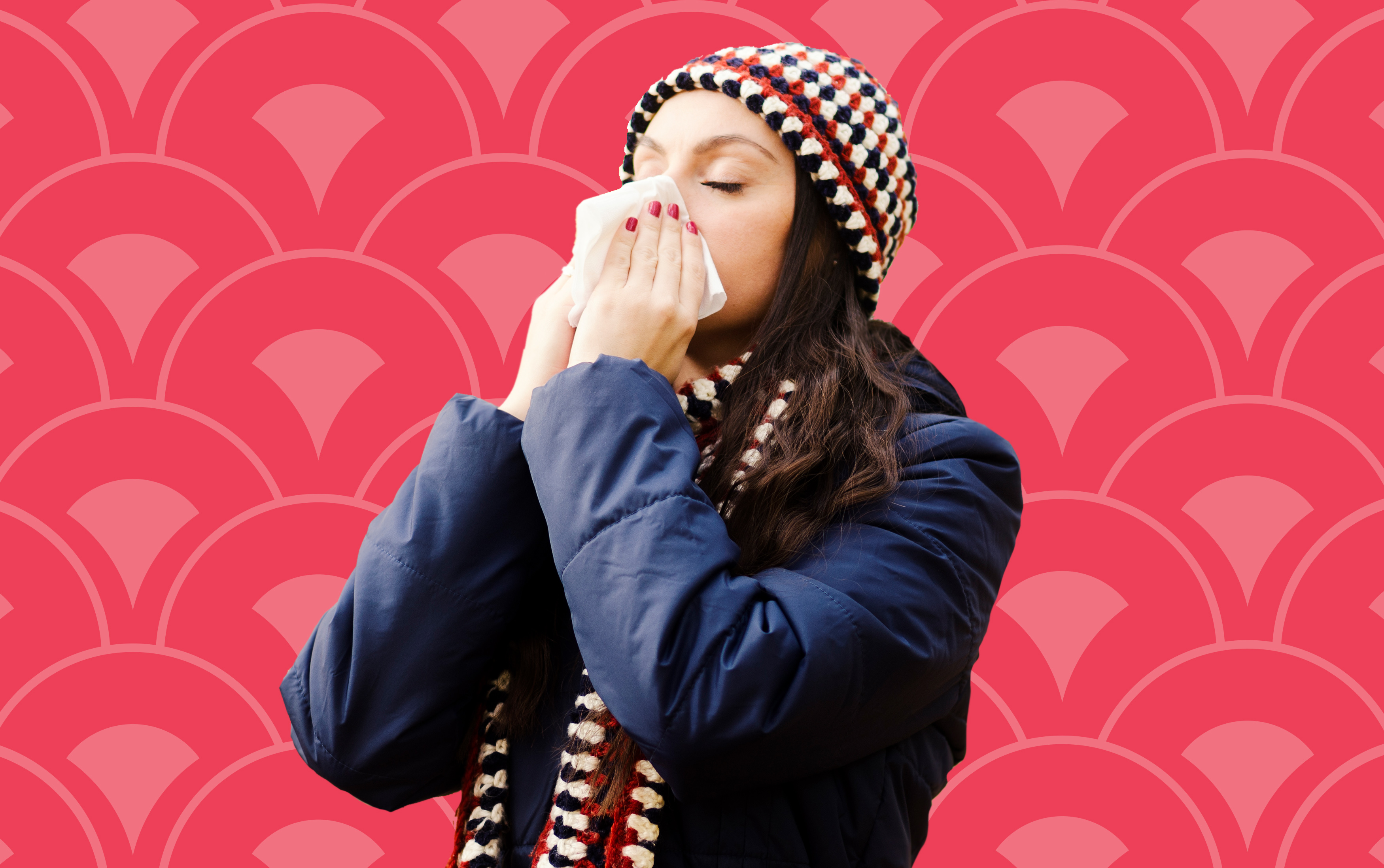 woman wearing navy coat sneezing into tissue against red background
