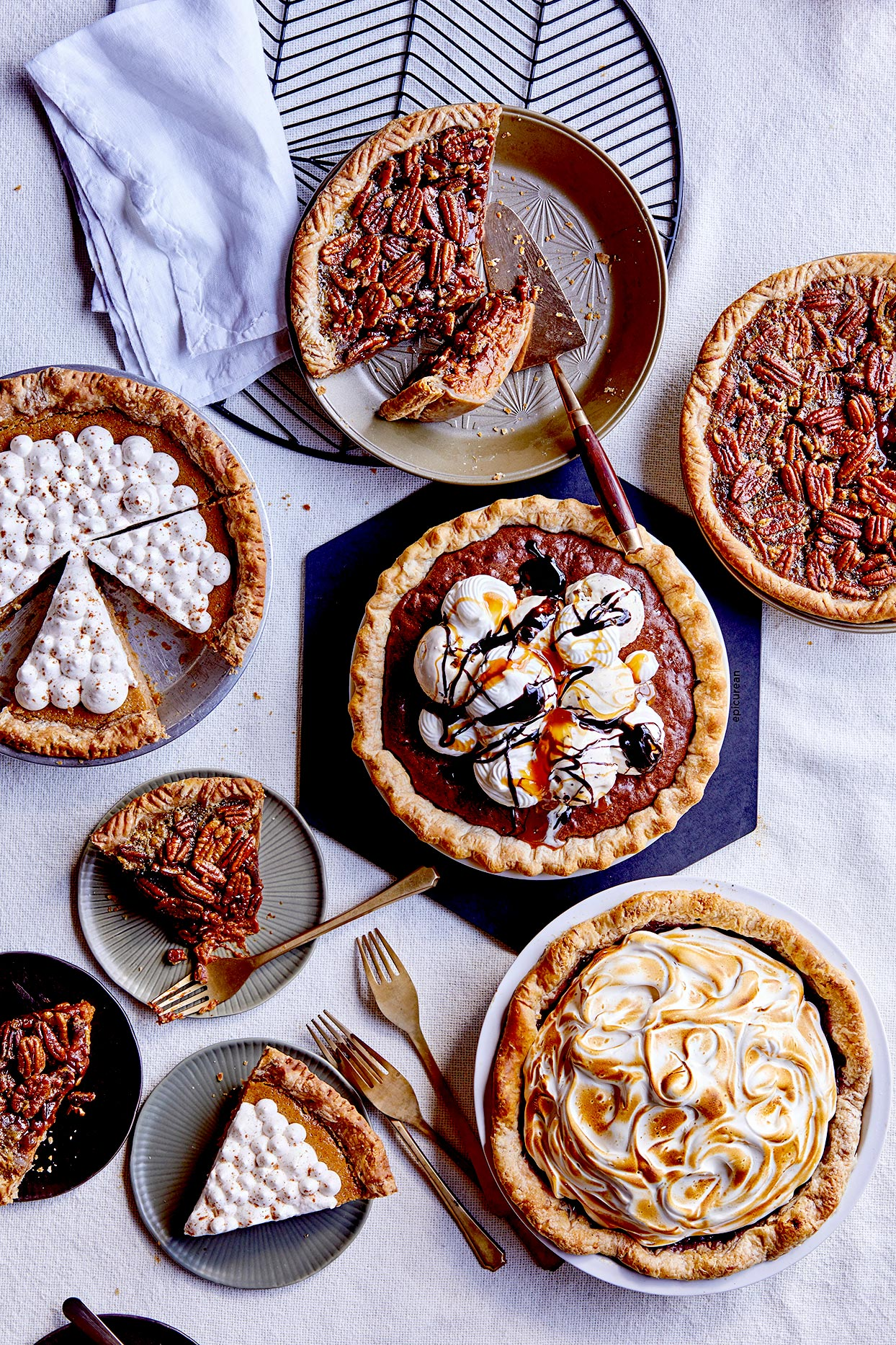 Five pies with slices on plates