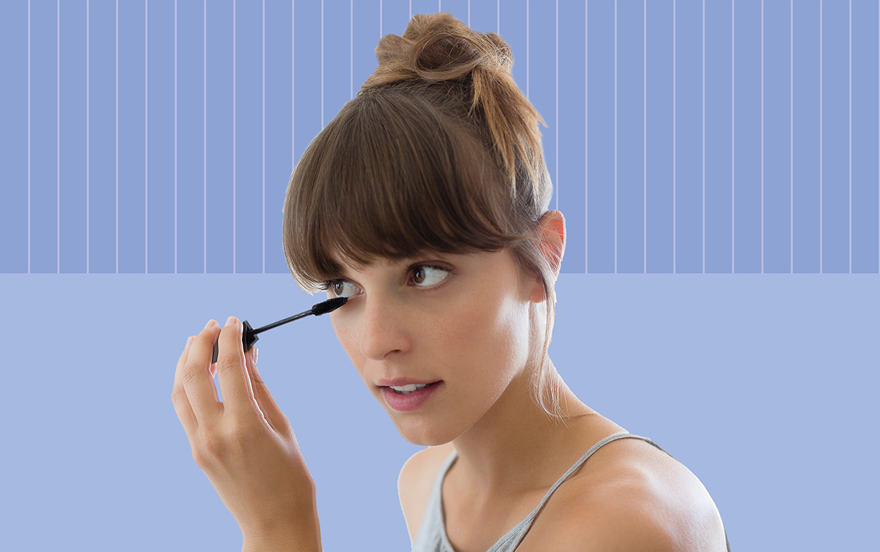 woman with brown hair applying mascara