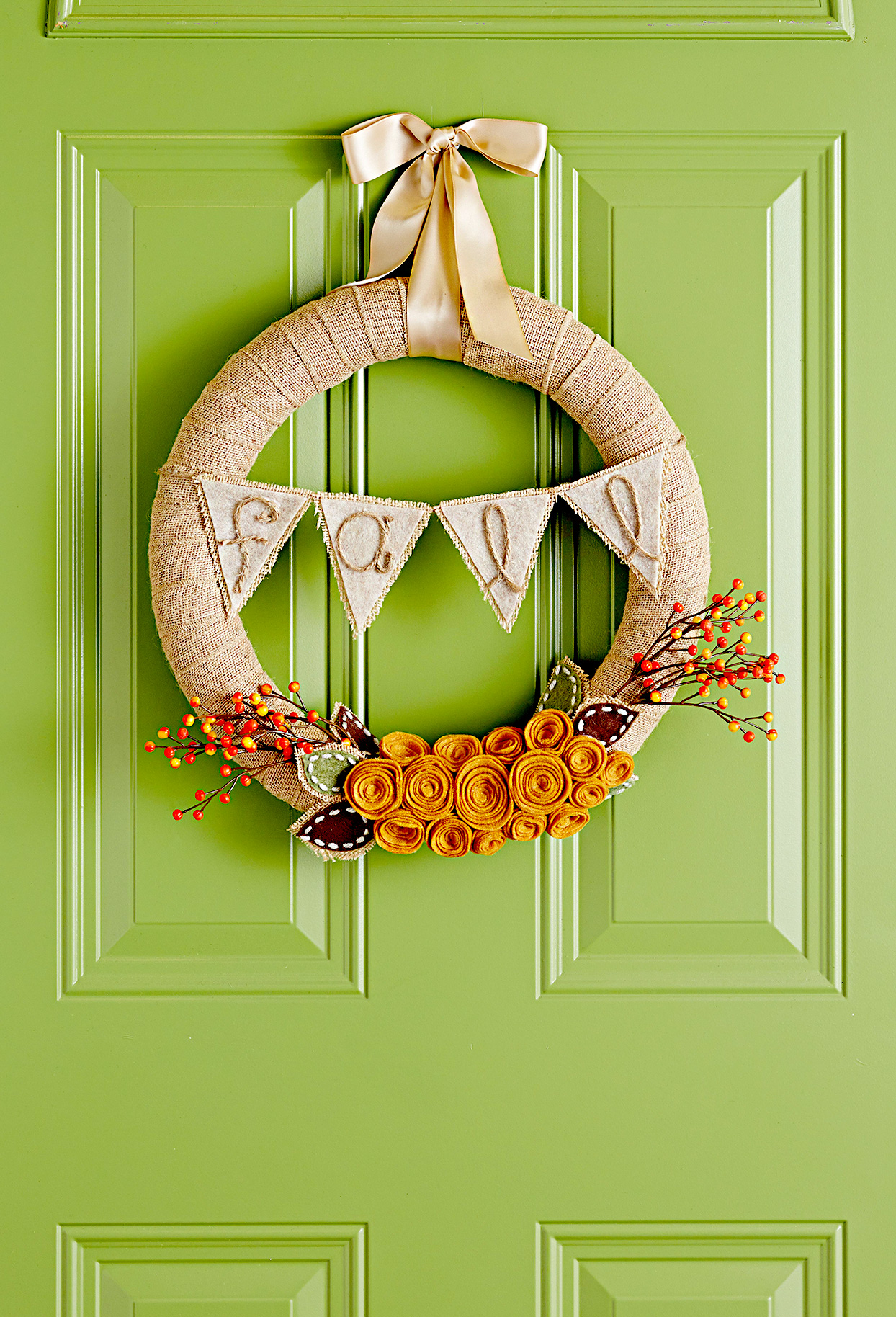 Fall wreath with flowers and bow on green door