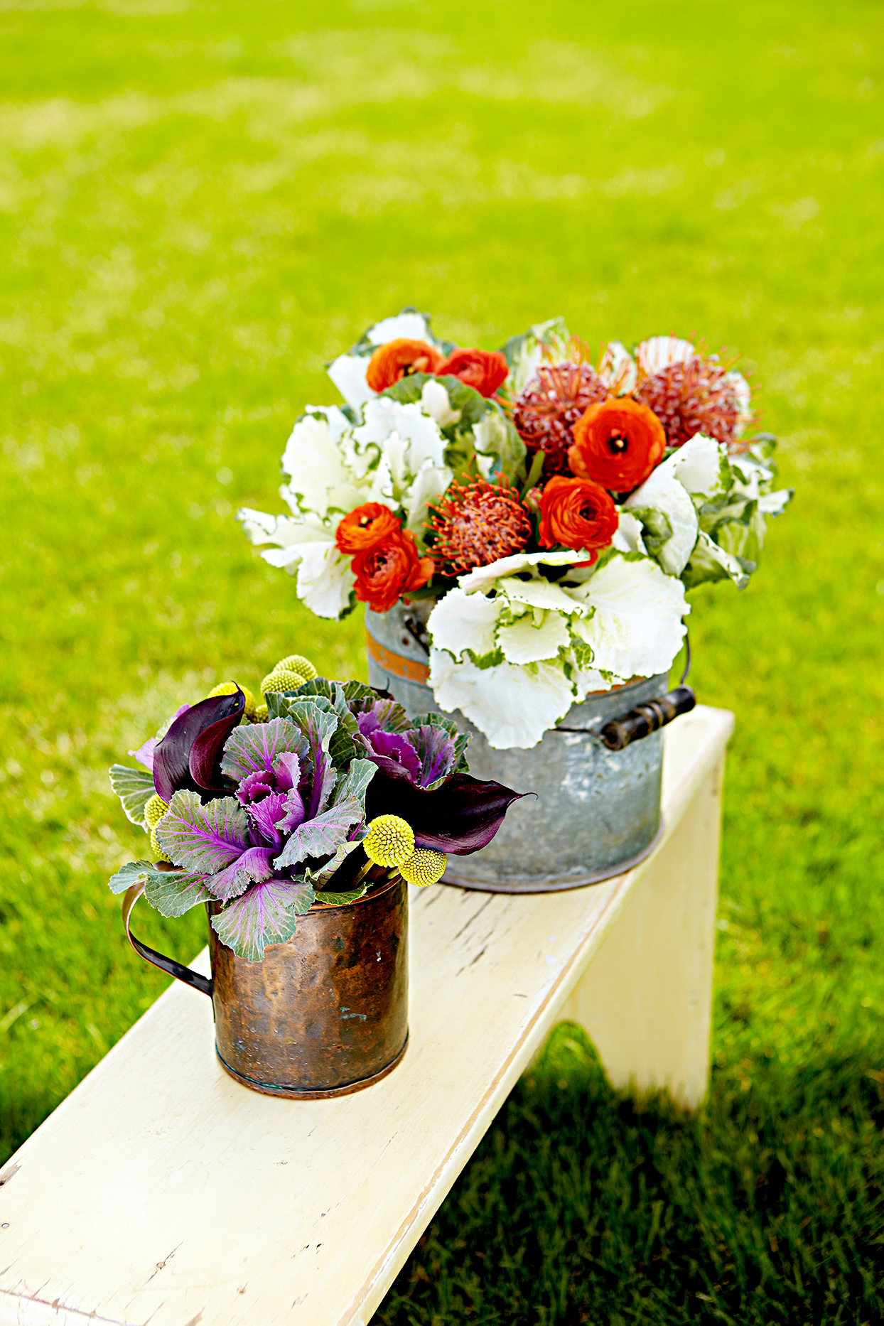 Two metal buckets with flowers