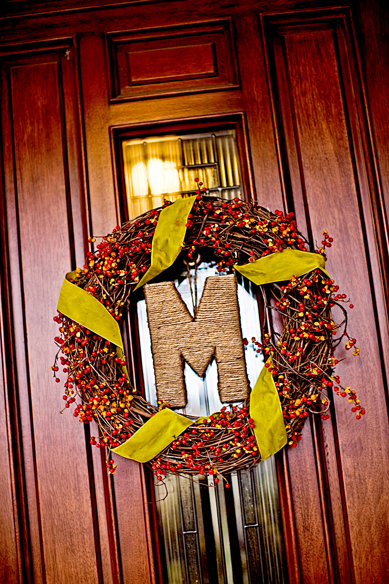 """Front door wreath made of berries and branches around """"M"""""""