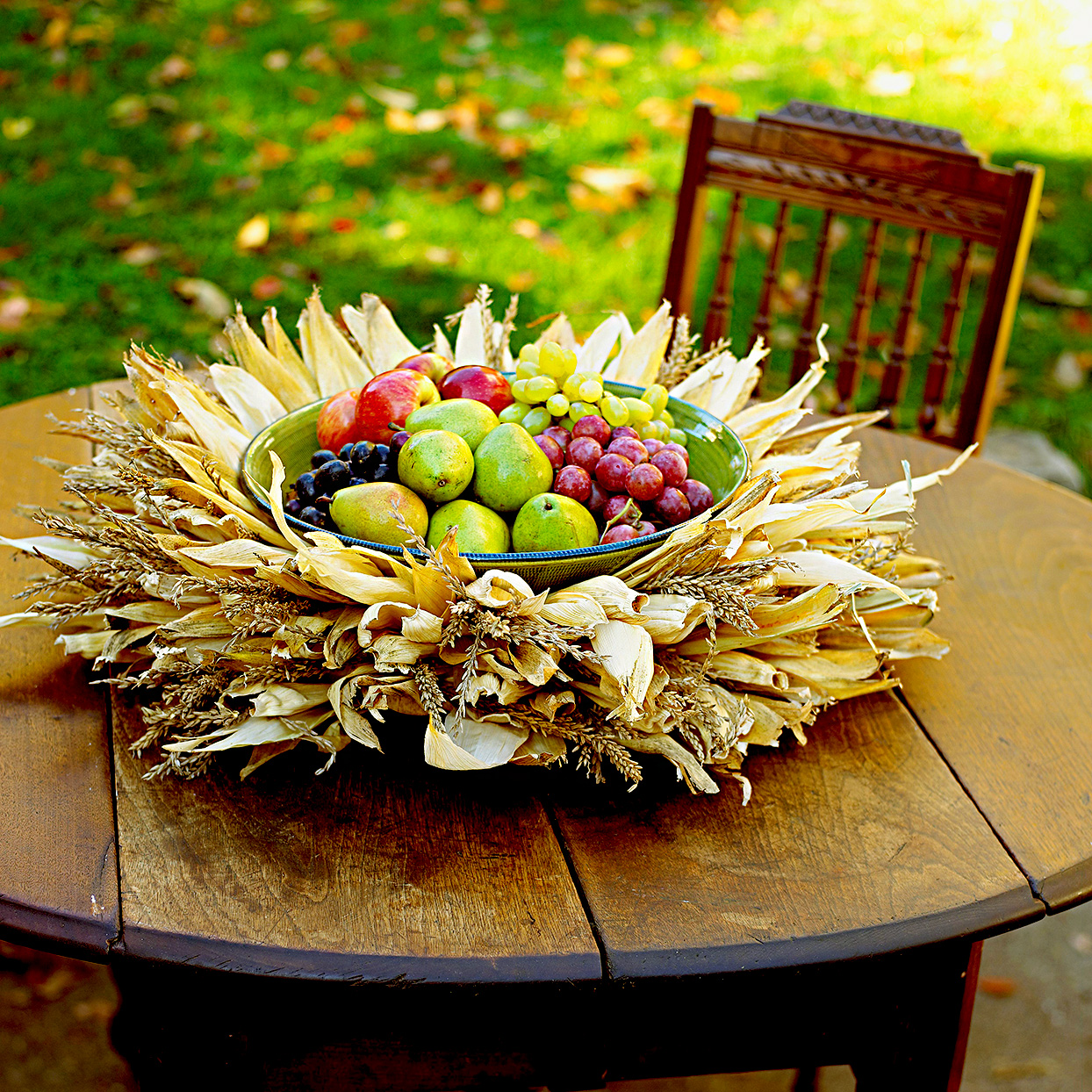 Wooden outdoor table with fall leaves and fruit centerpiece