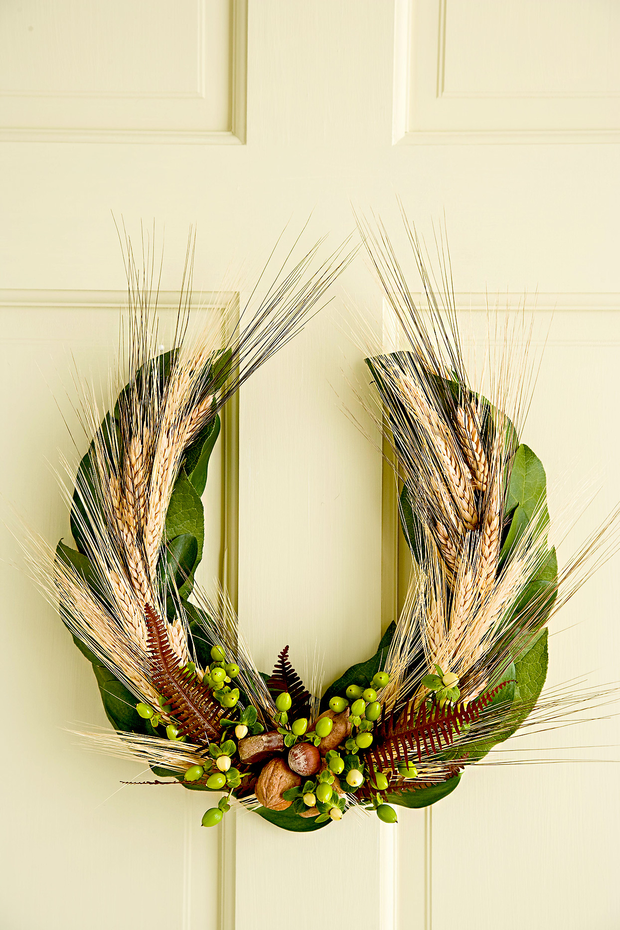 White door with green leaf wreath and wheat