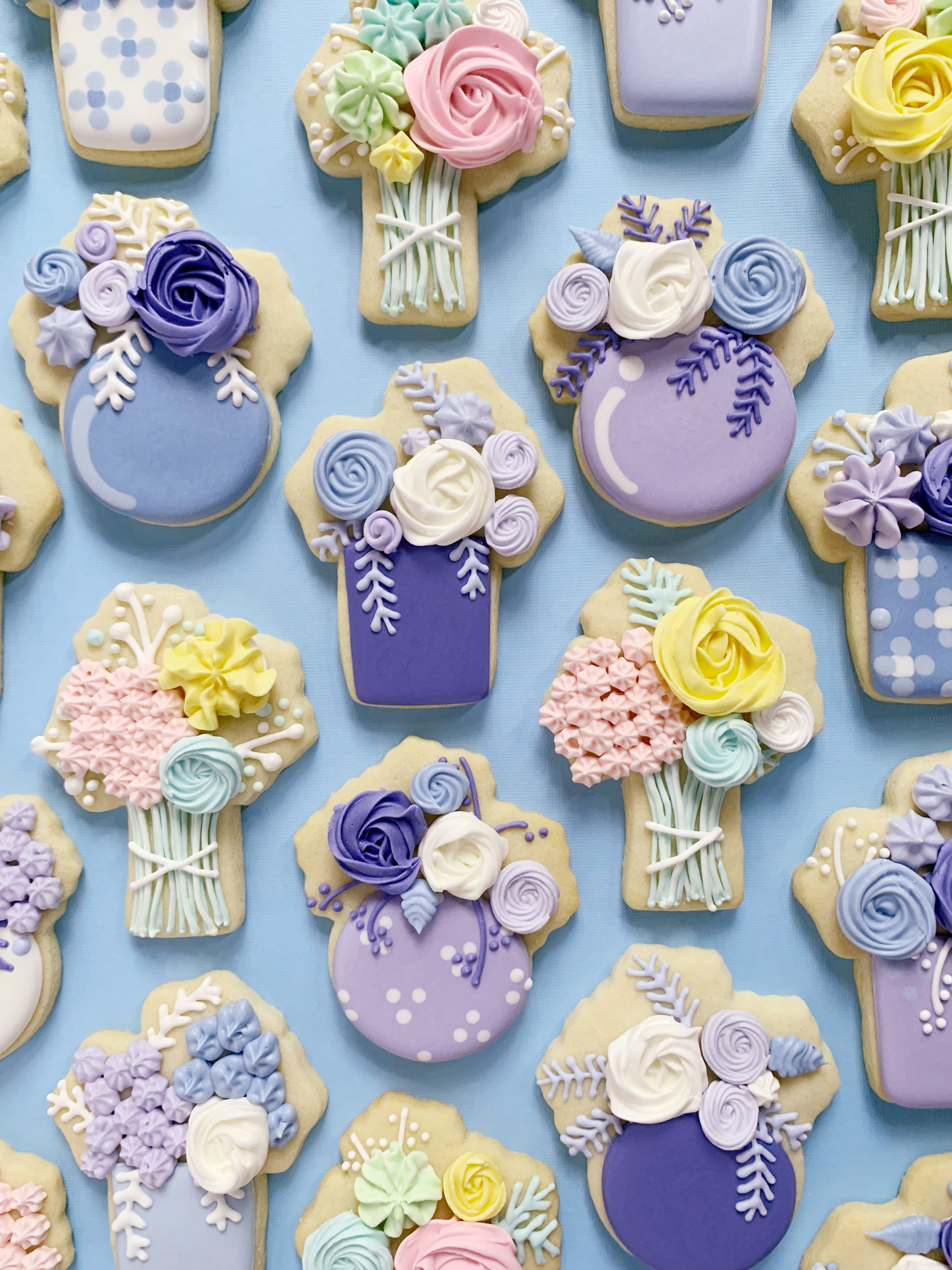cookies decorated to look like bouquets of flowers on a purple background