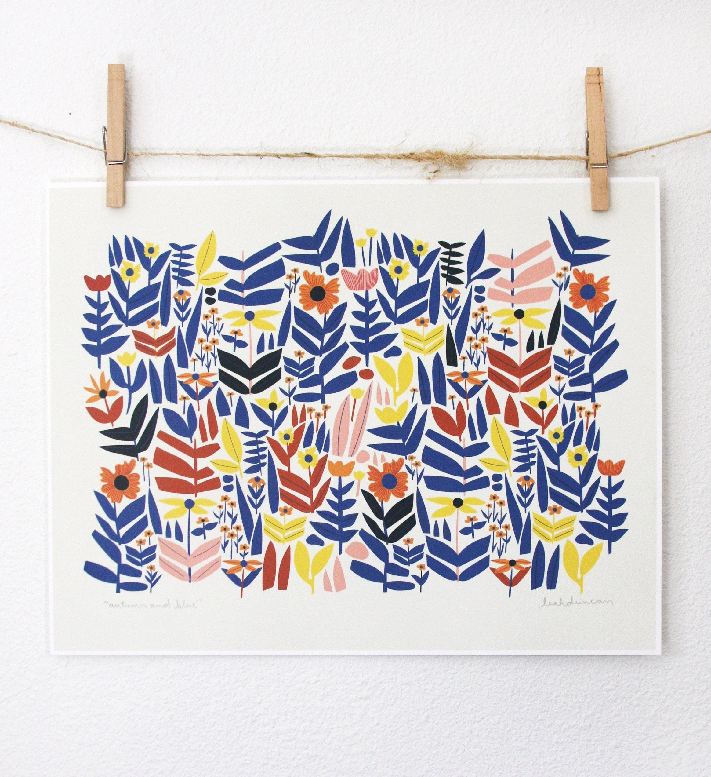 blue and red abstract art printed on a white piece of paper, hanging from twine and wood clips