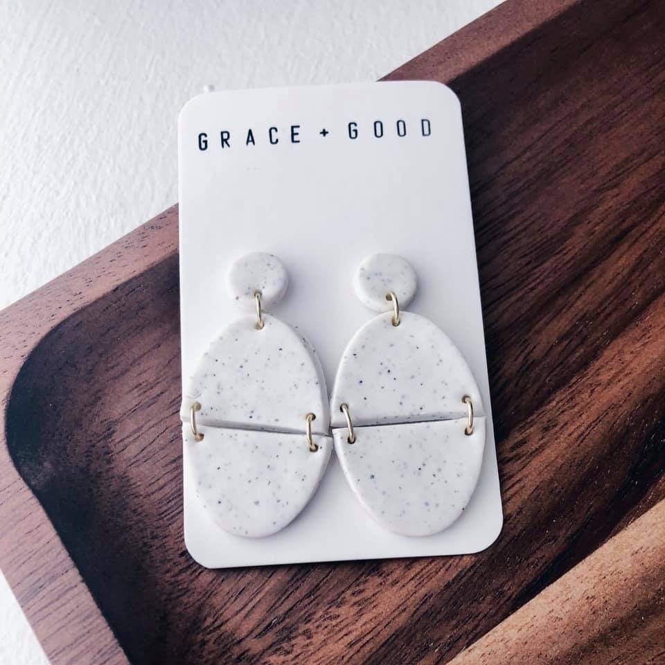 a pair of oval shaped white clay earrings attached to a white card that says grace and good