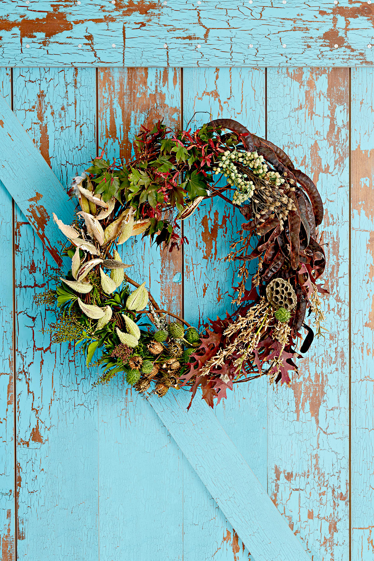 Wreath made of leaves, seed pods, and plants