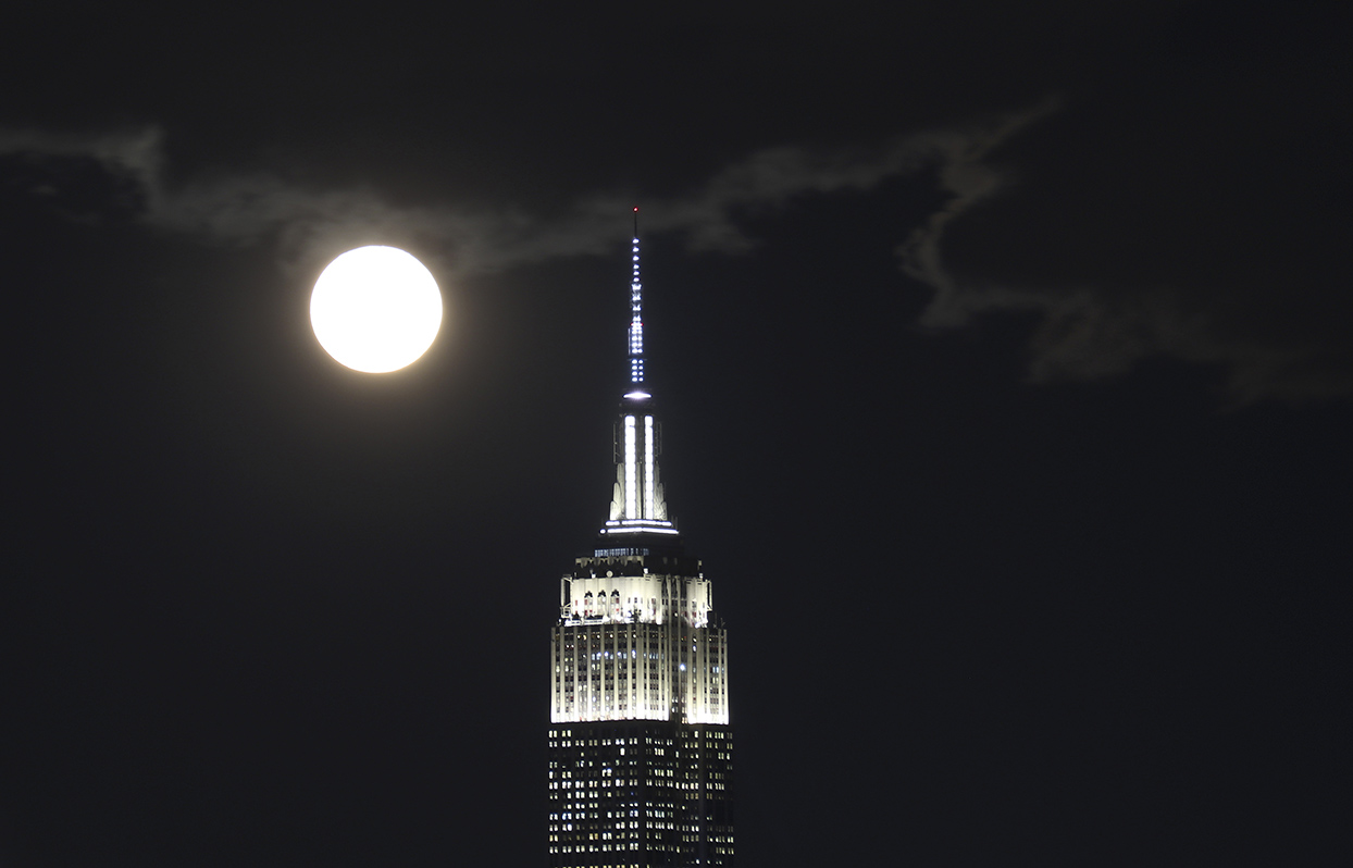 full moon behind empire state building