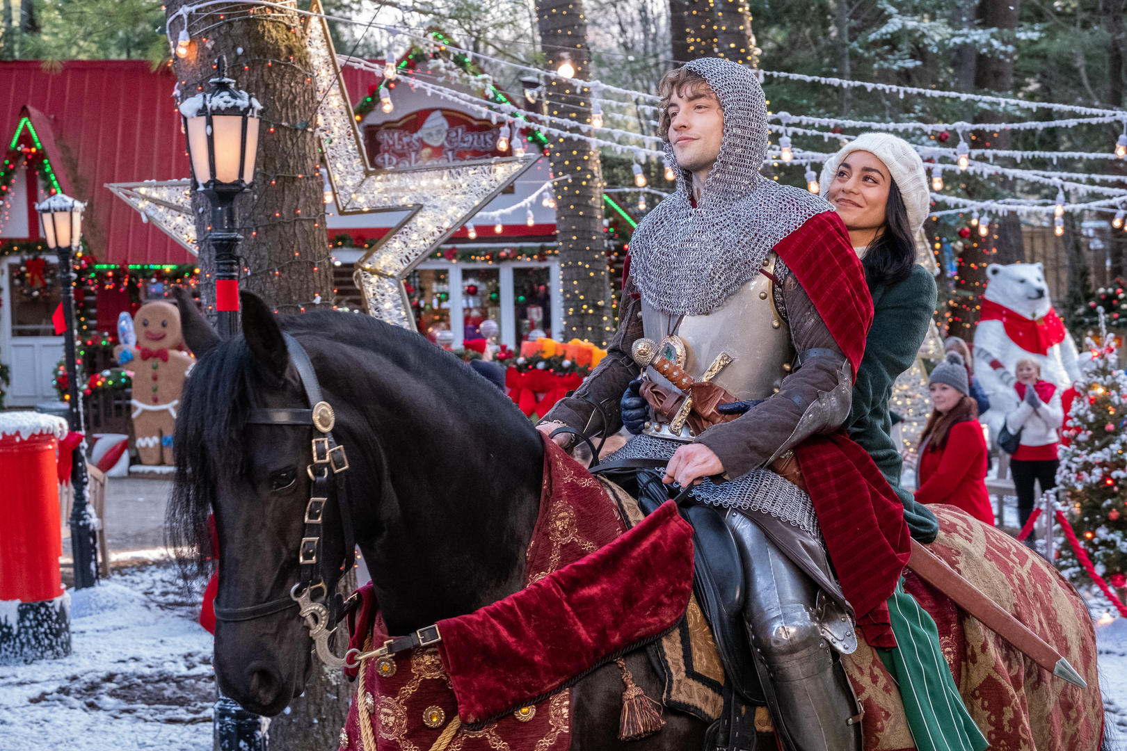 josh whitehouse and vanessa hudgens wearing coats and riding on a horse in front of christmas lights