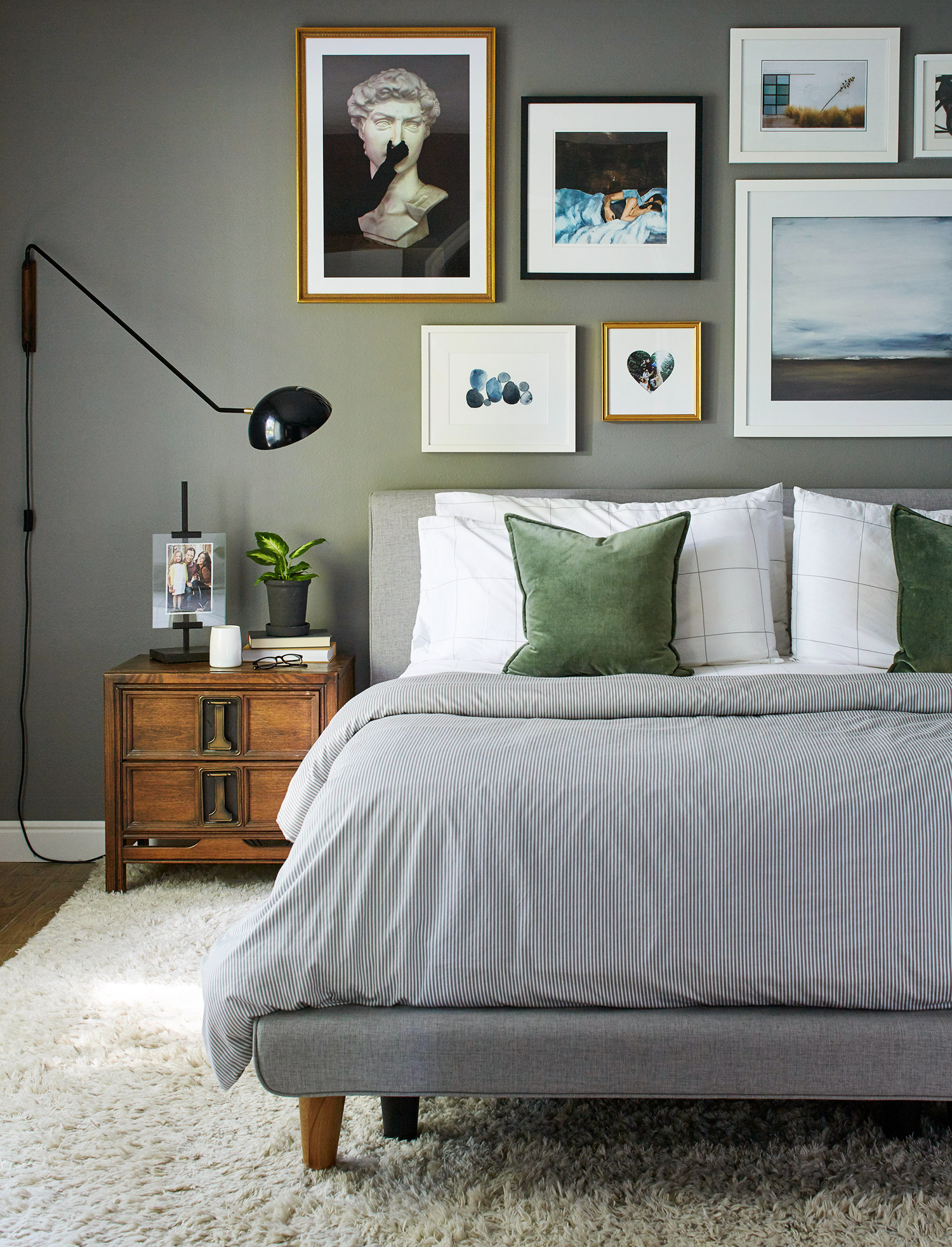 gray bedroom with green pillows bed