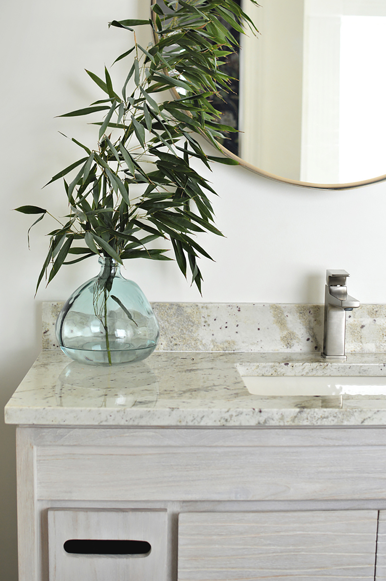 bathroom counter and sink area with glass vase and plant