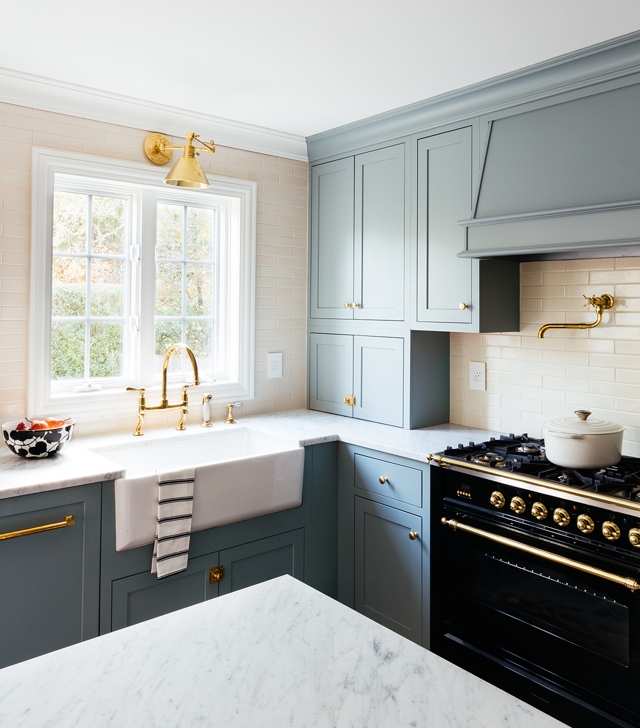 kitchen with white farmhouse sink blue-gray cabinets and black range