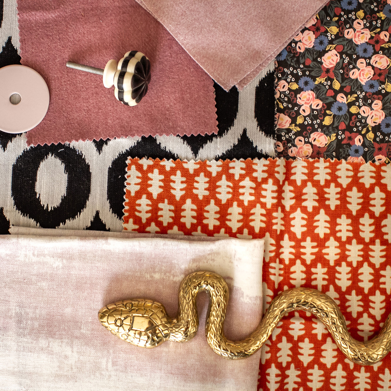 black hardware pull and brass snake on top of solid pink and multicolored pattern fabric swatches