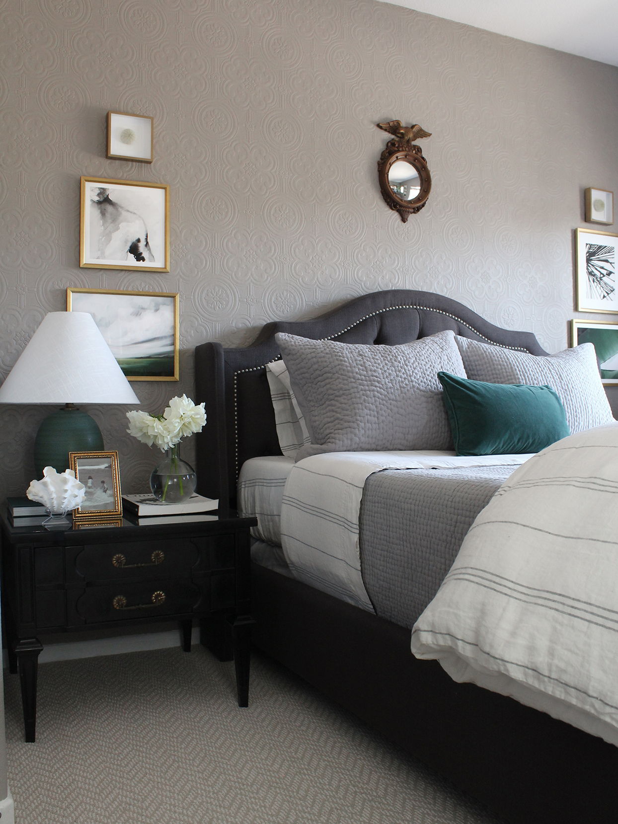 bedroom with gray walls gray headboard black nightstand with table lamp and gold-framed art hung on wall