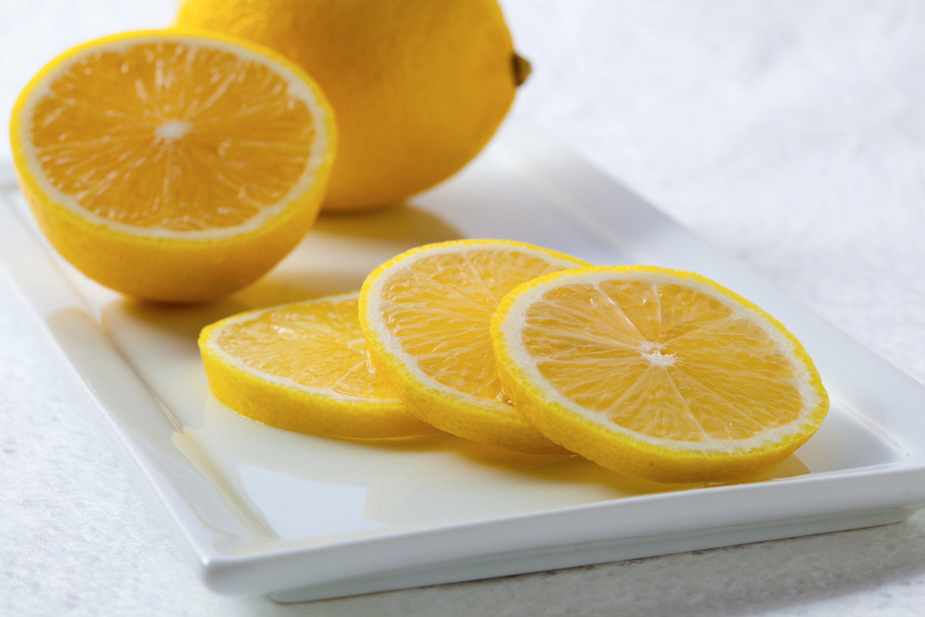 slices of lemon with whole lemon on cutting board