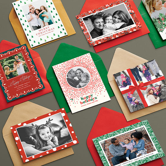 seven holiday cards with red, brown, and green envelopes