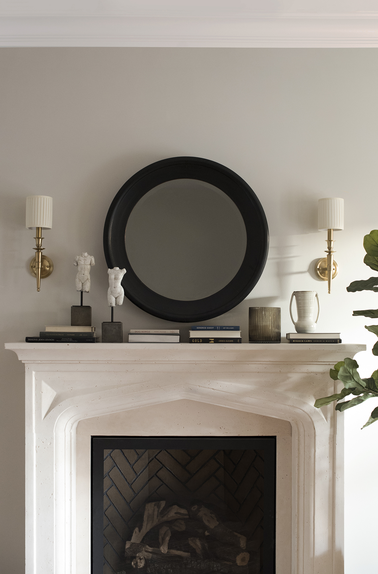 white fireplace against light gray wall with round black mirror above