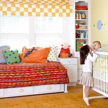 big sister on tiptoe to kiss little brother in crib in Ultimate Nursery