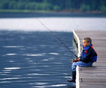 Little boy fishing alone, sitting on dock, rubber boots dangling over water