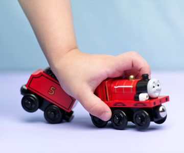 Child holding Thomas the Tank Engine toy