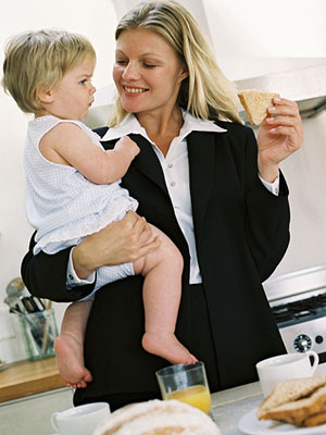 Mom in suit holds toddler, smiling