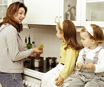mom cooking pasta with daughters