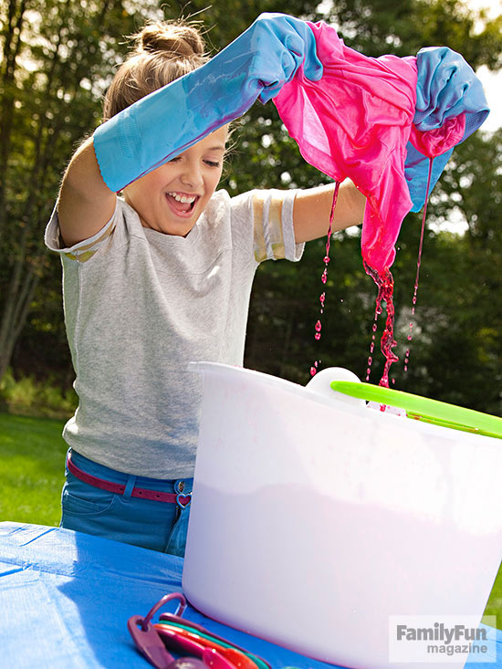 Girl dyeing shirt over white bucket