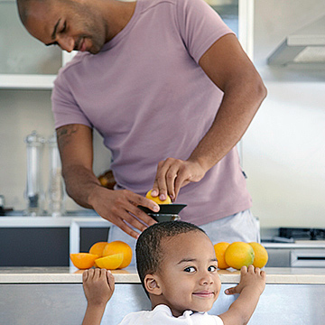 father and son making orange juice