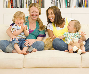 mothers playing with kids on couch