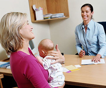 woman holding baby talking to pediatrician