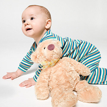 baby in stripes crawling with teddy bear